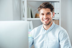 Businessman using laptop computer in office and looking at camera Royalty Free Stock Photography