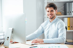 Businessman using laptop computer in office and looking at camera Stock Photos