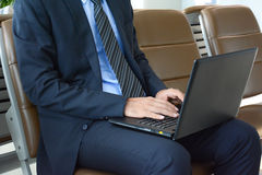 Businessman using laptop computer while sitting on the chair at the airport Royalty Free Stock Photos