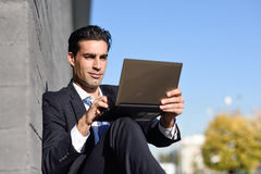 Businessman using a laptop computer sitting in the street Stock Images