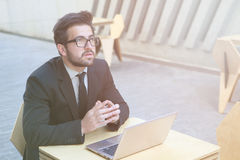 Businessman using laptop computer. Toned image of serious and confident businessman using laptop computer for work while sitting in restaurant or cafe. Freelance Stock Photography