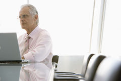 Businessman Using Laptop At Conference Table Royalty Free Stock Photo