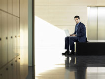 Businessman Using Laptop In Corridor Royalty Free Stock Image