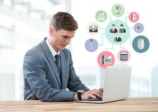 Businessman using laptop with digitally composite business icon Royalty Free Stock Images