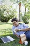 Businessman Using Laptop While Eating Sandwich At Park Stock Photos