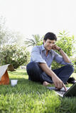 Businessman Using Laptop While Eating Sandwich At Park. Happy young businessman using laptop while sitting on grass at park Stock Image