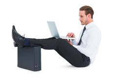 Businessman using laptop with feet up on briefcase Royalty Free Stock Photography