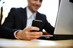 Businessman using laptop. Focus on smartphone. Royalty Free Stock Photos