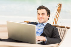 Businessman using laptop on the hammock Stock Photography