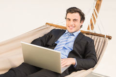 Businessman using laptop on the hammock Stock Images