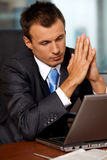 Businessman using laptop with hands clasped in office Stock Images