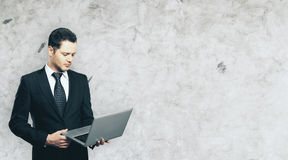 Businessman using laptop. Handsome young businessman using laptop on concrete wall background with copy space. Technology concept Royalty Free Stock Photography