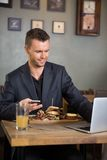 Businessman Using Laptop While Having Food In Stock Images