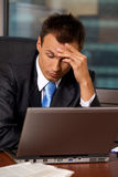 Businessman using laptop with head in hands Royalty Free Stock Photo