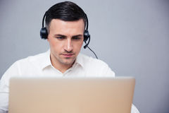 Businessman using laptop in headphones Royalty Free Stock Image