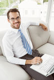 Businessman using laptop in living room Royalty Free Stock Photography