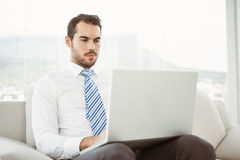 Businessman using laptop in living room Stock Photos