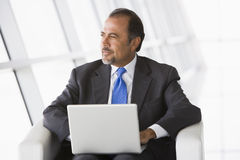Businessman using laptop in lobby Stock Images