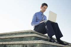 Businessman Using Laptop On Marble Staircase Stock Images