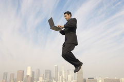 Businessman Using Laptop In Midair With Cityscape In Background. Full length side view of businessman using laptop in midair with cityscape in background Stock Photos