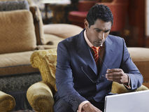 Businessman Using Laptop. Middle aged businessman sitting in lobby and working on laptop Stock Images