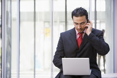 Businessman using laptop and mobile outside Royalty Free Stock Photo