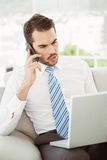 Businessman using laptop and mobile phone in living room Stock Photo