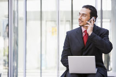 Businessman using laptop and mobile phone outside. Office Stock Images