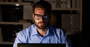 Businessman using laptop at night stock video