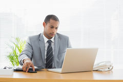 Businessman using laptop at office desk Stock Photo
