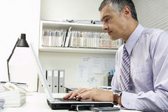 Businessman Using Laptop At Office Desk Stock Photos