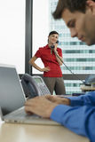 Businessman using laptop in office, focus on woman using telephone in background, smiling, side view Royalty Free Stock Photos