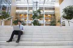 Businessman Using Laptop On Office Steps Stock Image
