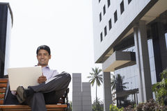 Businessman Using Laptop Outdoors. Portrait of happy young businessman using laptop outside office building Stock Photography