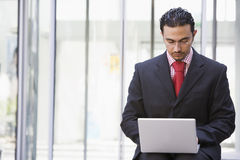 Businessman using laptop outside. Office Stock Image