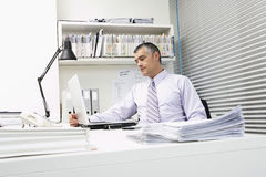 Businessman Using Laptop With Paperwork At Desk Stock Images