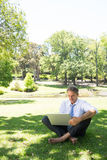 Businessman using laptop at park. Full length of mature businessman using laptop while sitting on grass in park Stock Image