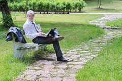 Businessman using laptop in a park. A young handsome businessman using laptop in a park Stock Photos