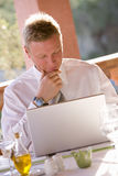 Businessman using laptop on restaurant balcony Royalty Free Stock Photos