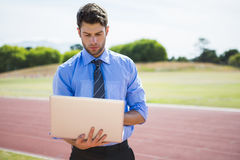 Businessman using a laptop on the running track. Businessman standing on a running track and using a laptop Stock Photos