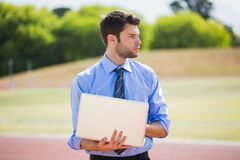 Businessman using a laptop on the running track. Businessman standing on a running track and using a laptop Royalty Free Stock Images