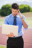 Businessman using a laptop on the running track. Businessman standing on a running track and using a laptop Stock Images