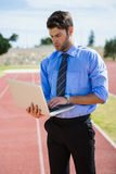 Businessman using a laptop on the running track. Businessman standing on a running track and using a laptop Royalty Free Stock Photo