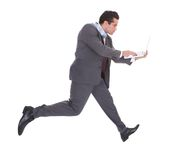 Businessman using laptop while running Royalty Free Stock Photos