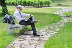 Businessman using laptop sitting on a bench. A young handsome businessman using laptop sitting on a bench in a park Royalty Free Stock Photography