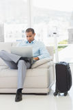 Businessman using laptop sitting on sofa waiting to depart on business trip Stock Photos