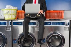 Businessman Using Laptop While Sitting On Washing Royalty Free Stock Photos