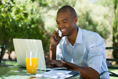 Businessman using laptop and smart phone at restaurant Stock Photography