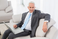 Businessman using laptop on sofa at home Royalty Free Stock Photo