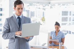 Businessman using laptop standing in office. With women working behind him Royalty Free Stock Image